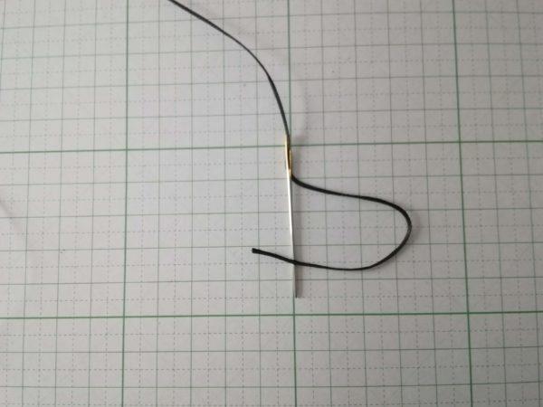 蝋引き糸を通したあと、先端を針に刺す