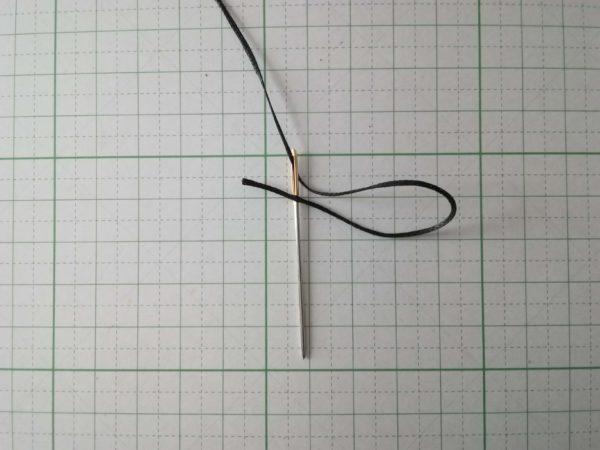 蝋引き糸を先端に刺し、上にあげる