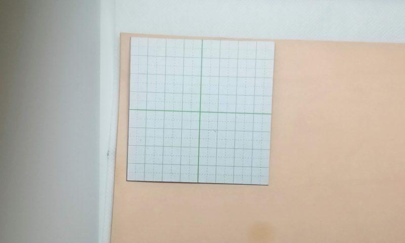 カットする革の上にコースターの型紙をおき、線をひく