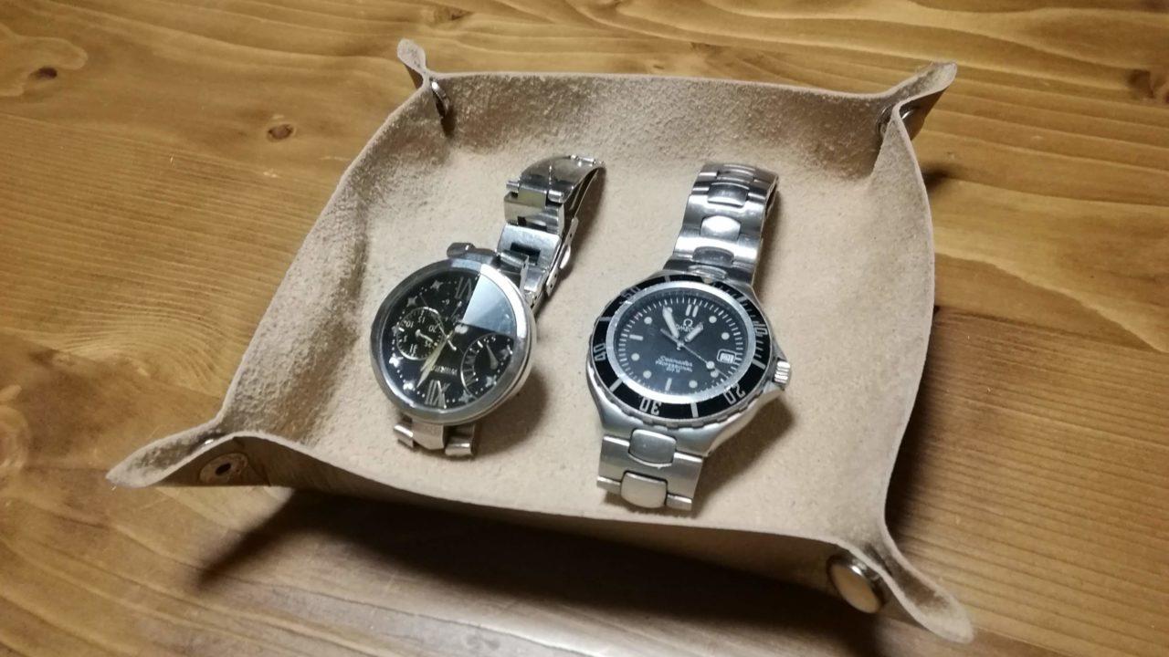 革のトレイにペア時計を置く