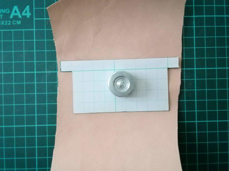 型紙を革にのせてお薬手帳ケースのカード収納部を裁断する線をひく